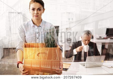I need a job. Gloomy unemployed woman holding a box with her belongings while her boss sitting in the background and drinking coffee