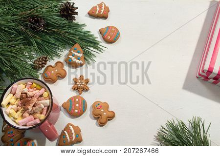 Festive Christmas and New Year backdrop. Green pine, sweet gingerbread cookies and cup of marshmallows on white background, top view free space on right. Presents and congratulation concept
