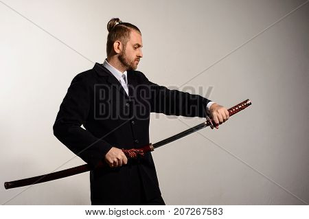 Male businessman wearing a suit pulls out a sword of Japanese samurai