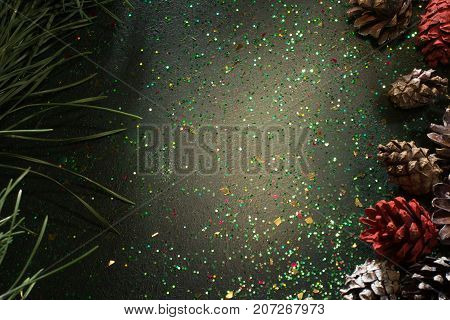 Festive backdrop for Christmas gift and greeting. Top view sparkled black background with pine and strobilas, free space in the middle. Celebration, presents and congratulation concept