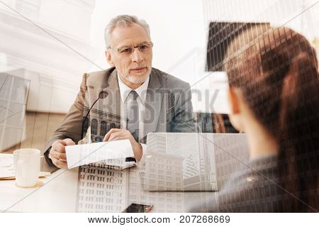 Reached understanding. Cheerful adult professional HR manager having a job interview with a nice female candidate while enjoying the talk in the office