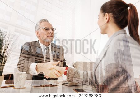 Right decision. Positive professional boss shaking hand of a new female employee while sitting at the table and expressing gladness