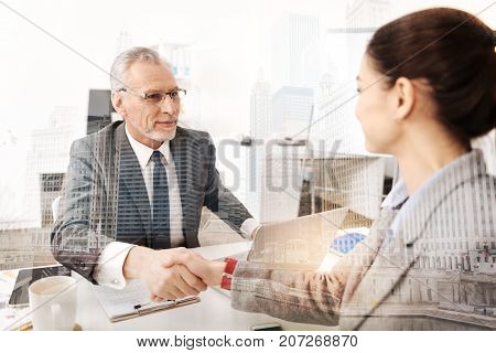 Corporate rules. Cheerful adult boss sitting at the table and having a firm handshake with a new female employee