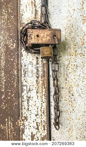 Old padlock and chain locking door are rusty and insecure safety concept