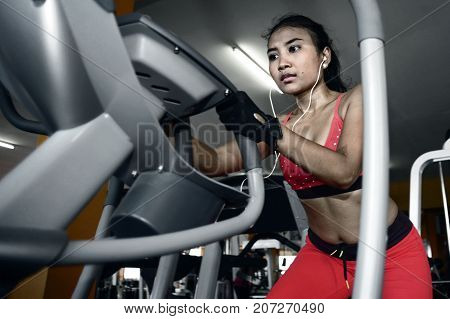 young sexy and sweaty Asian woman training hard at gym using elliptical pedaling machine gear in intense workout exercise wearing sport top and gloves in fitness and healthy lifestyle concept