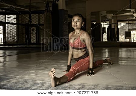 harsh grunge edit of young sweaty Asian woman in sport clothes stretching and split legs to relax muscles on gym dojo after hard training workout and healthy sporty lifestyle concept