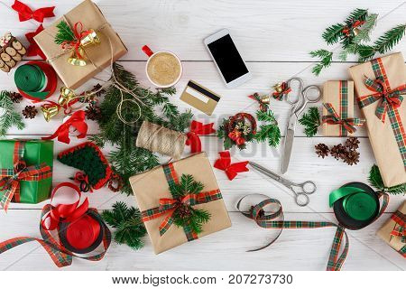 Creative diy hobby and online shopping background. Top view on messy table with christmas ornaments, ribbons, present boxes, mobile and credit card.