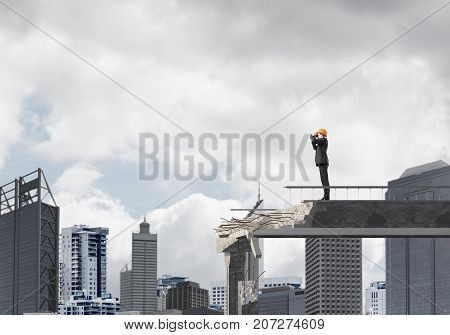 Young engineer in suit and helmet looking in binoculars while standing on broken bridge with cityscape on background. 3D rendering.