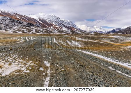 A picturesque autumn landscape with a rocky dirt road through the steppe in the mountains golden trees on the slopes and the first snow