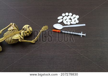 Skull and drugs with insulin syringe. Next to them are a spoon with white powder which is similar to heroin on wooden backgroundtouch - up in still life concept.