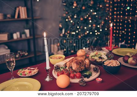 All is ready for x mas! Generously served table with yummy fresh dishes and glasses of wine are ready for the romantic feast dinner with tasty treats dishes candles nice decorated loft room indoors