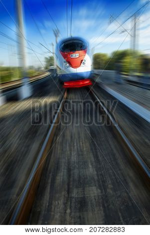 Amazing beautiful impressive front view on moving white red blue beautiful high speed passenger train. Motion blur. Moscow high speed trains rail tracks. Russian high speed train. Train in motion