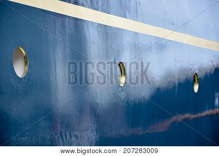 Portholes On A Blue Wall On A Ship