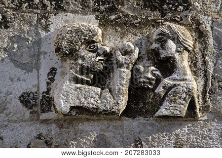 Adam takes apple from Eva stone relief on the west wall of Diocletian palace in Split Croatia
