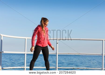 Outdoor relax sport fintess concept. Woman in sports suit standing on dyke next to sea resting after active workout.