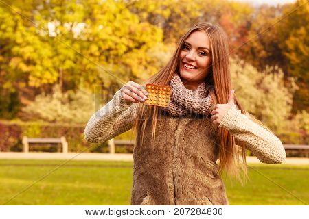 Woman in autumn park holding vitamins medicines showing how to deal with seasonal autumnal fever and supporting immunity during cold days