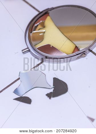 Destruction low self esteem accident conflict concept. Broken mirror lying on tiled floor