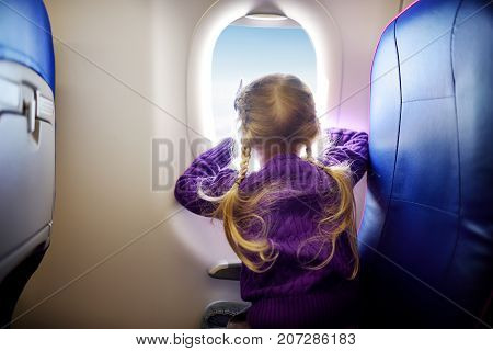 Adorable Little Girl Traveling By An Airplane. Child Sitting By Aircraft Window And Looking Outside.