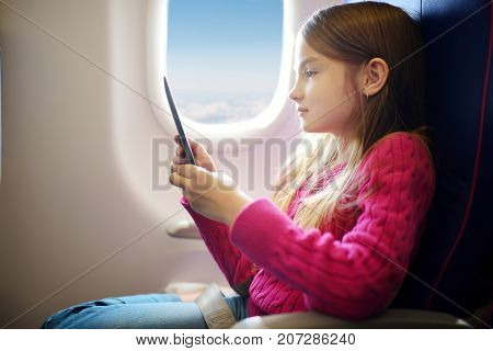 Adorable Little Child Traveling By An Airplane. Girl Sitting By Aircraft Window And Reading Her Eboo