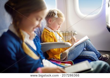 Adorable Little Girls Traveling By An Airplane. Child Sitting By Aircraft Window And Drawing A Pictu