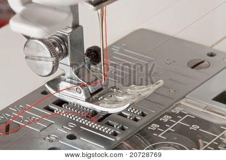 Hilo en la aguja de la máquina de coser Closeup