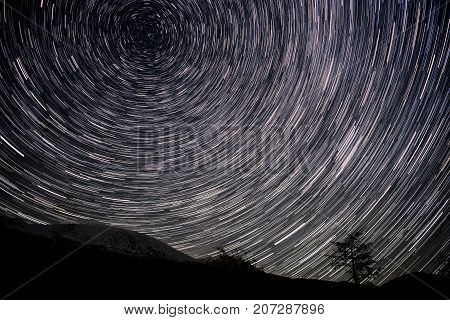 Beautiful night view with traces of stars revolving around the polar star in the form of circular tracks against the background of mountains and tree shot with a long exposure
