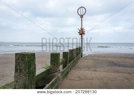 Old Wooden Poles Covered With Moss At A Beach With A Metal Octopus On A Pole
