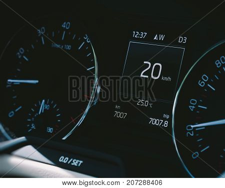 Car speedometer close-up with the needle pointing a 20 km/mph speed driving electric car digital display screen