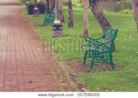 Metal long chair located on green grass beside walkway or footpath at public park for recreation.