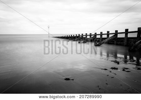Long Exposure At Portobello Beach With Groynes And A Calm Sea In Black And White