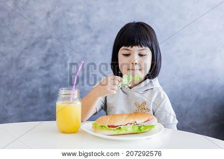 Cuttle Black Hair Little Girl Having Breakfast And Eat Lettuce