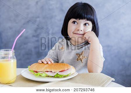 Cute Black Hair Little Girl Eating Sandwich At Home