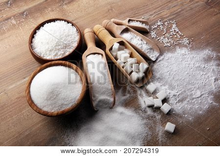 Bowl And Scoop With White Sand And Lump Sugar On Brown Wooden Background