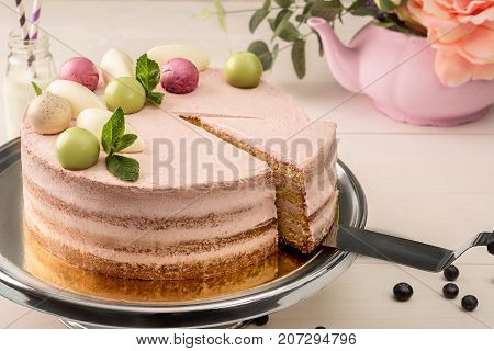 Pink cake with mint and decorative sweet balls from above on a plate, close-up. Still life