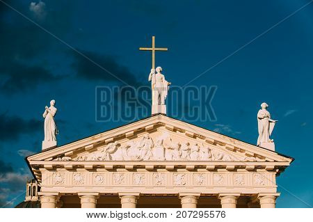 Vilnius Lithuania. Close Pediment Of Cathedral Basilica Of St. Stanislaus, St. Vladislav With Three Statues - St. Elena With Cross, St. Stanislaus, St. Casimir, Relief Sculpture Decoration, Blue Sky