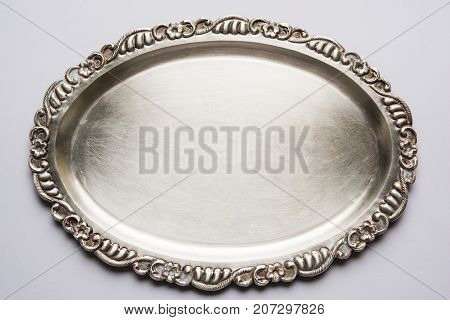Stock photo of empty or blank silverware or oval shape plate with decorative border, isolated over white background, selective focus