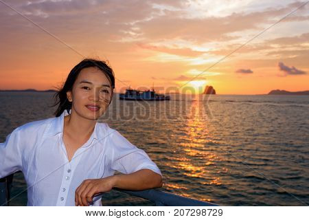 Beautiful nature of colorful sky and sun at sunset over the sea women tourist on the deck of a large passenger boat while cruising to Koh Samui Island in Surat Thani province Thailand