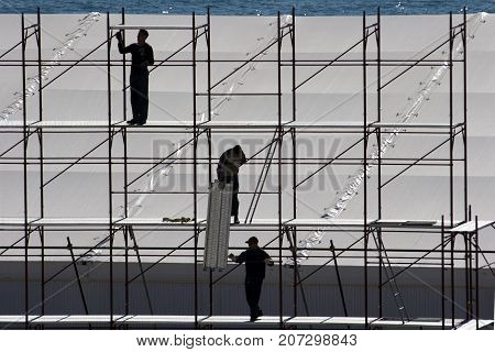 Silhouettes of workers on iron aluminum scaffold