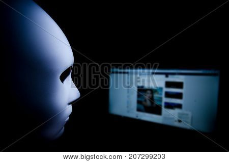 You never know who is behind your screen. Anonymous mask to hide identity in front of a computer - internet criminal and cyber security threat concept.