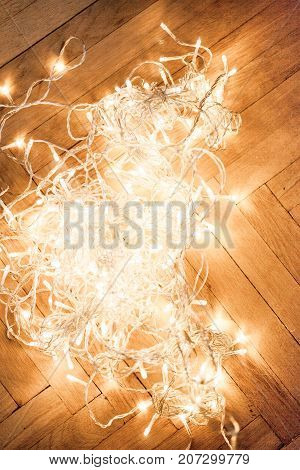 Christmas composition with glowing lights garland on a old antique wooden parquet floor sparkling garland.