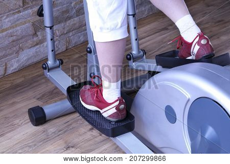 Young woman is intensely doing exercises on an elliptical cross trainer in the gym