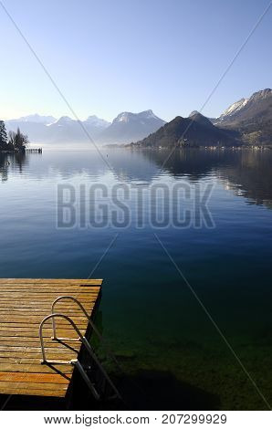 Annecy lake from Talloires and wooden pontoon for swimming winter landscape Savoy France