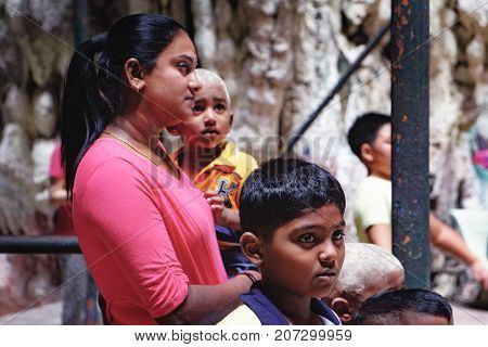 Batu Caves, Malaysia - February 7, 2016: Malaysian Hindu people visit to the the most popular Hindu shrines - Batu Caves. Hindu family of Mom and her little sons inside the caves