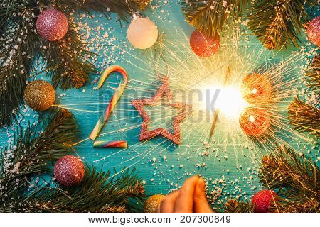 Image of blue wooden surface with spruce branches, figures from caramel, candles, burning Bengal fire, colorful balls