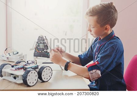 Stem education. Concentrated boy creating robot at lab. Early development, diy, innovation, modern technology concept
