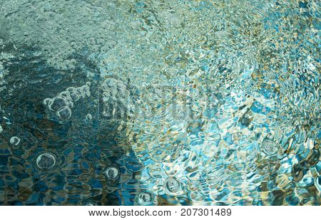 Bubbles on water surface in the pool from falling water