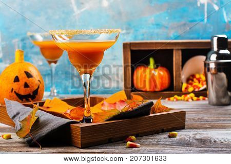 Autumn pumpkin margarita cocktail with halloween decor on wooden table. Copy space