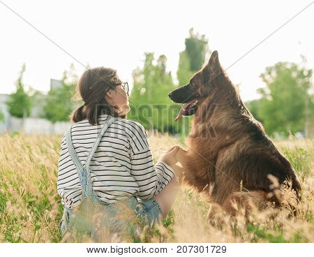 Portrait of young beautiful woman sitting and hugging her German Shepherd dog. Happiness and friendship. pet and woman. Back view