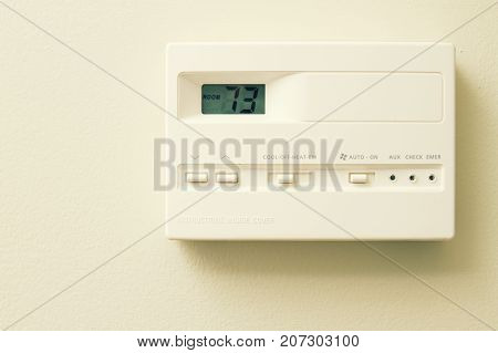 a thermostat temp gauge on wall of home.