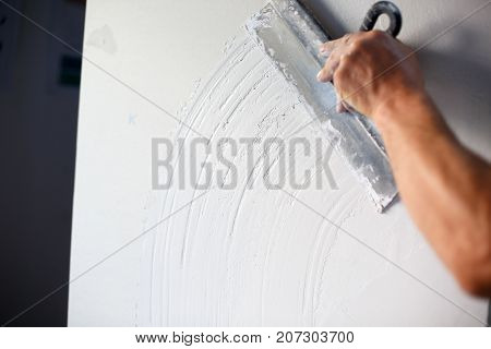 The strong hand of a man with a trowel constructs a white wall with a sham. Plastering a wall. Close-up of man's hand.
